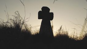 Tbig stone cross in the grass at sunset stock footage