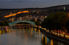 Tbilisi κεντρικός η γέφυρα ειρήνης έκανε από το γυαλί, τον ποταμό Mtkvari, και το διάσημο αρχαίο φρούριο narikala στο λόφο city l Στοκ Φωτογραφίες