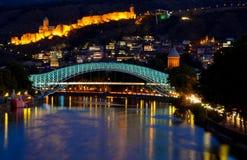 Tbilisi κεντρικός η γέφυρα ειρήνης έκανε από το γυαλί, τον ποταμό Mtkvari, και το διάσημο αρχαίο φρούριο narikala στο λόφο city l Στοκ Εικόνες