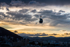 Tbilisi cableway at night. Cableway gondola (cabin) floats through the colorful late sunset sky. There can be seen Tbilisi cityscape below immersed in darkness Royalty Free Stock Photography