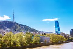 Tbilisi, Geórgia - 19 de abril de 2017: Opinião do panorama de Tbilisi e de Rio Kura Marco moderno - hotel Tbilisi de Biltmore Foto de Stock