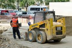 TBILISI, GEÓRGIA - 19 DE JULHO DE 2017: Homem no formulário de trabalho perto do equipamento do reparo da estrada Fotos de Stock Royalty Free