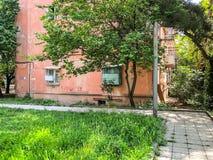 TBILISI, GEÓRGIA - - 17 DE MAIO DE 2018: A jarda de uma casa, árvores da flor, grama verde, carros na jarda Primavera na cidade Imagens de Stock
