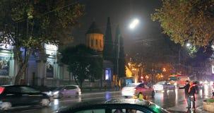 Tbilisi, Geórgia - 22 de novembro de 2018: Tráfego na rua da avenida de Rustaveli da noite Opinião da noite da igreja de Kashveti filme