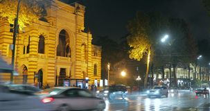 Tbilisi, Geórgia - 22 de novembro de 2018: Tráfego perto de Opera nacional Georgian e do teatro de bailado de Tbilisi na noite filme