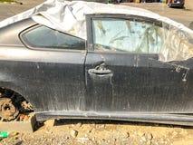 TBILISI, GEORGIË - - 17 MEI, 2018: Een oude gebroken die auto met geteerd zeildoek met een band op de bonnet wordt behandeld bij  Royalty-vrije Stock Afbeelding