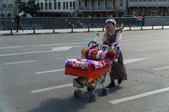 Tbilisi, 25 Georgië-Sep, 2016: Verkoopster van kronen die een kar met goederen op de weg duwen Stock Foto's