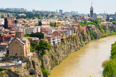Tbilisi, Georgia aerial skyline view with old traditional houses. Panoramic skyline with old traditional houses over Mtkvari or Kura river and Metekhi church Stock Photos