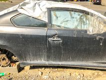 TBILISI, GEORGIA - - 17 DE MAYO DE 2018: Un coche roto viejo cubierto con la lona con un neumático en el capo parqueó en el camin imagen de archivo libre de regalías