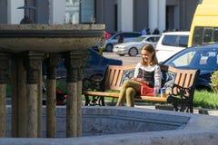 Tbilisi, Georgia 25 de septiembre de 2016: la muchacha con el teléfono se sienta en el banco en el cuadrado de la libertad Imagenes de archivo