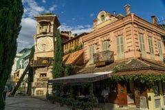 TBILISI, GEORGIA - 25 DE SEPTIEMBRE DE 2016: La torre de reloj que se inclina de Rezo Gabriadze Marionette Theatre con el café de Foto de archivo