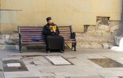 Tbilisi, Georgia 25 de septiembre de 2016: Sacerdote georgiano que lee un libro que se sienta en un banco Imagen de archivo