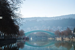 TBILISI, GEORGIA - JANUARY 5, 2017: A view to an old town of Tbilisi. Peace bridge and mountains around the city from Kura`s embankment early in the morning Stock Photos
