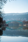 TBILISI, GEORGIA - JANUARY 5, 2017: A view to an old town of Tbilisi. Peace bridge and mountains around the city from Kura`s embankment early in the morning Stock Images