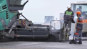 TBILISI - GEORGIA 15 June 2016 - Clip of heavy equipment asphalt laying machine dropping blacktop tar stock video footage