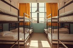 Light in window of hostel bedroom with clean white bunk beds for students and tourists Royalty Free Stock Photos
