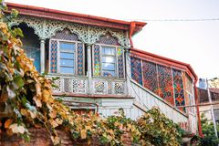 Exterior of an old house with wood balcony in the old town of Tbilisi, Georgia. Tbilisi, Georgia - 8 October 2016: Exterior of an old house with wood balcony in Stock Images
