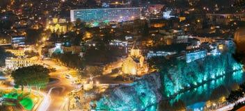 Tbilisi, Georgia Panorama de la tarde de la noche, vista iluminada del acantilado de Metekhi Fotos de archivo libres de regalías