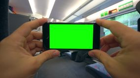 Hands Holding a Phone with a Green Screen on the Train. Tbilisi, Georgia - 15 September 2017: Hands holding using a smapthone with a green screen on the train Royalty Free Stock Photos