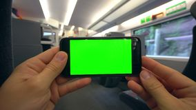 Hands Holding a Phone with a Green Screen on the Train. Tbilisi, Georgia - 15 September 2017: Hands holding using a smapthone with a green screen on the train Royalty Free Stock Photo