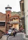 Tbilisi, Juma mosque. TBILISI, GEORGIA - SEPTEMBER 23, 2018: Many people, tourists and locals, walk on narrow streets of old town Tbilisi near the Juma mosque royalty free stock photo