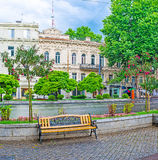 Tbilisi after the rain. The rainy Rustaveli Avenue with lonely bench, surrounded by flower beds and blooming trees, with the historic edifices on background Stock Photos
