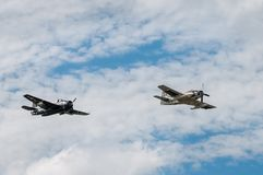 TBM复仇者和AD4 Skyraider飞行横跨多云天空 免版税库存图片