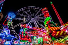 THRILL RIDES WITH COLORFUL LIGHTS. A tcarnival, or travelling funfair is an amusement show that may be made up of amusement rides, food vendors, merchandise stock image