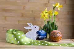 Tchèque fait main fait maison a peint les oeufs et le lapin en bois, pseudonarcissus jaune de narcisse en fleur Photos stock