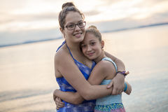 Tchildren sister hugging at the sunset beach. Two children sister hugging at the sunset beach Stock Image