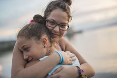 Tchildren sister hugging at the sunset beach. Two children sister hugging at the sunset beach Stock Images