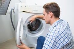 Técnico que repara una lavadora Fotografía de archivo libre de regalías