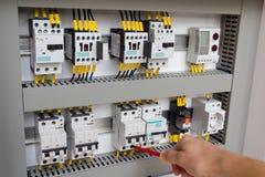 Técnico que trabaja en la cabina eléctrica Fotografía de archivo