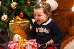 Tddler-Mädchen mit Geschenken nähern sich Weihnachtsbaum Stockfotografie