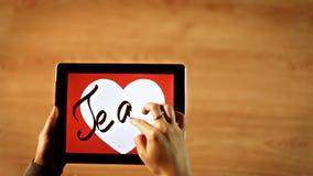 Te amo calligraphy. Female writing inside white heart on tablet stock video