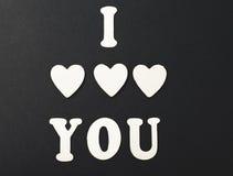 Te amo con las letras y los corazones de madera en fondo negro Foto de archivo libre de regalías