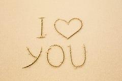Te amo escrito en la arena amarilla mojada de la playa Foto de archivo libre de regalías