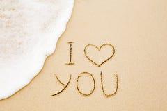 Te amo escrito en la arena amarilla mojada de la playa Foto de archivo