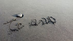 Te amo. I love you written on a black sand beach with a heart shaped rock near Royalty Free Stock Image