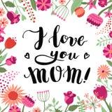 ¡Te amo mamá! entinte el fondo y la tarjeta manuscritos de las letras del cepillo con las flores y las plantas Fotografía de archivo