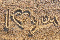 Te amo mensaje escrito en arena de oro Imagenes de archivo