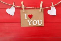 Te amo tarjeta del mensaje sobre el tablero de madera rojo Fotos de archivo