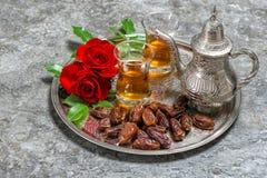 Te daterar frukter, och den röda rosen blommar Islamisk feriedecorat Fotografering för Bildbyråer