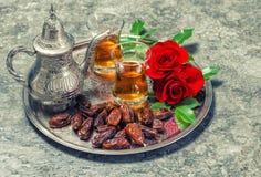 Te daterar frukter, och den röda rosen blommar Orientalisk gästfrihet lurar Royaltyfri Fotografi