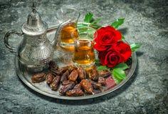 Te daterar frukter, och den röda rosen blommar Orientalisk gästfrihetvin Arkivfoton