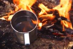 Te eller kaffe i metall rånar värmer upp på stenen på brasa Varm drink på naturen Te som dricker i öppen luft Campa i skymning ro Royaltyfria Foton