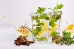 Te för ny mintkaramell för två glass koppar med citronen och honung på vit bakgrund Arkivfoton