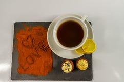 Te i en vit kopp med en citron och två smakliga muffin och woen Royaltyfria Bilder