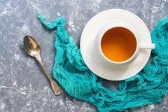 Te i en vit kopp med en turkosservett En kopp av örtte på vit bakgrund ovanför sikt royaltyfria bilder