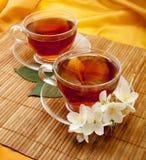 Te i koppar för ett exponeringsglas med jasmin blommar på matt bambu Fotografering för Bildbyråer
